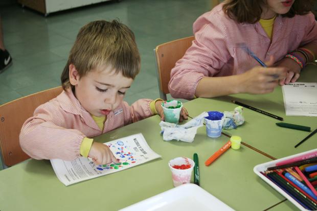 niños pintando las etiquetas Vi Solidari Masroig