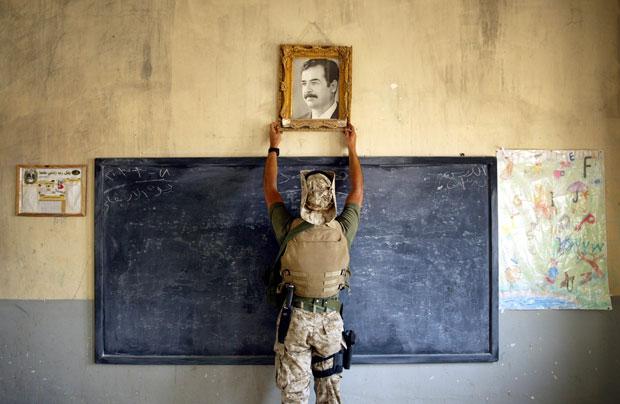 Chris Hondros – marine retirando la foto de Sadam Hussein en una escuela