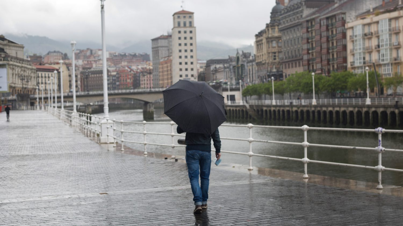 hombre caminando bajo la lluvia con una pieza de Rain of Bilbao en la mano