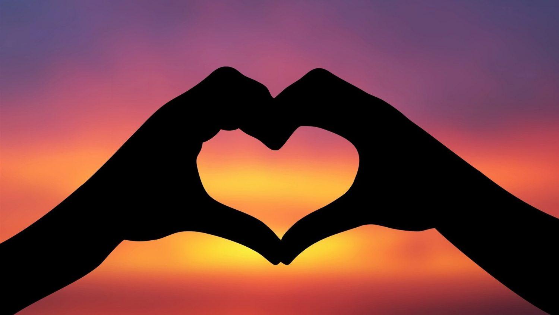 corazon-con-manos-al-atardecer