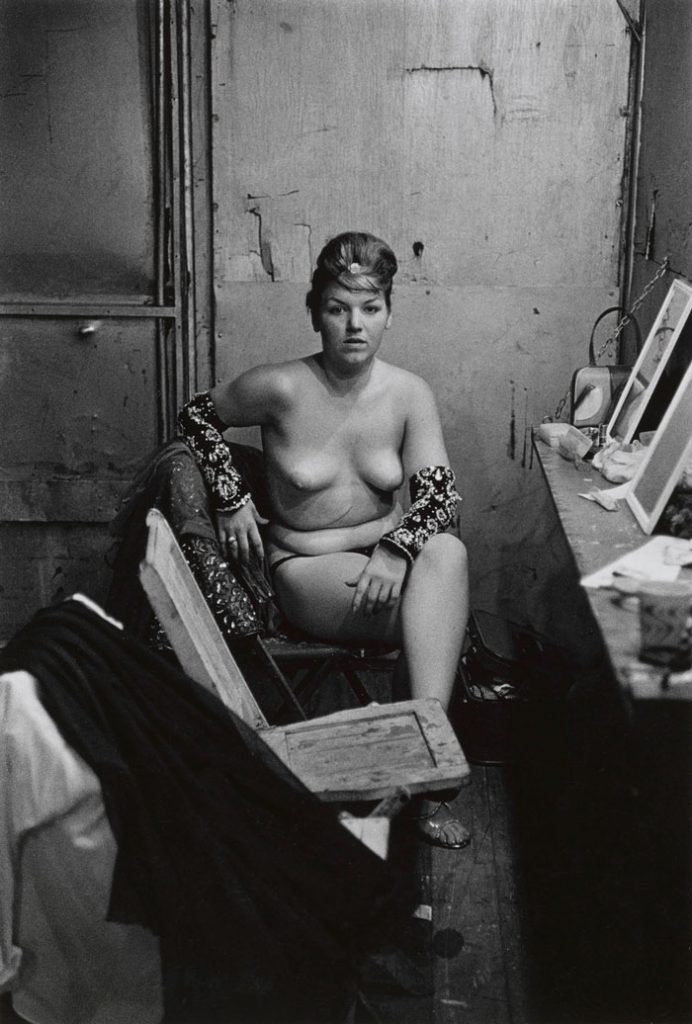 Stripper with bare breasts sitting in her dressing room, de Diane Arbus