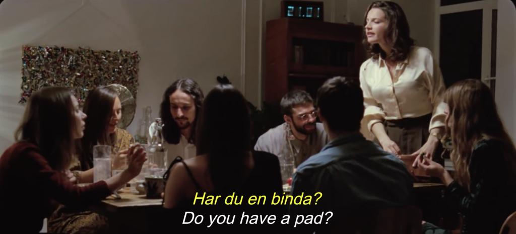 Mujer pidiendo una compresa en una cena con amigos del anuncio de Boodyform
