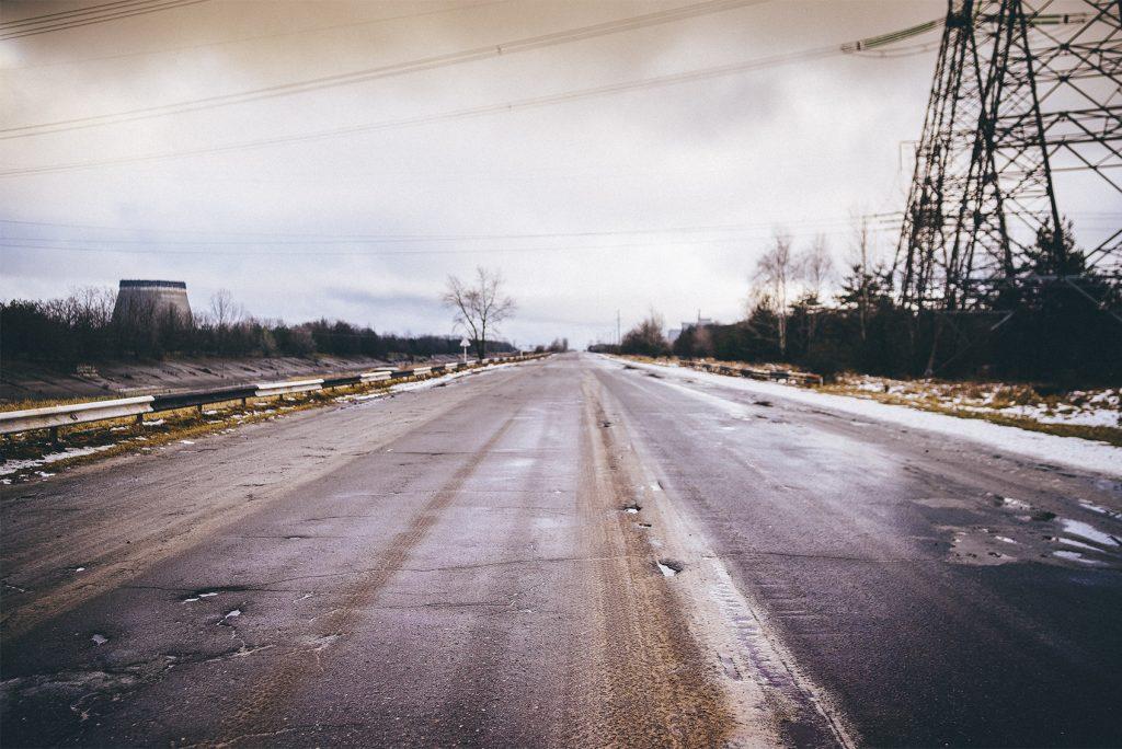 A la derecha la torre de enfriamiento para la quinta unidad de la central nuclear de Chernobyl, carretera que llega sarcófago.