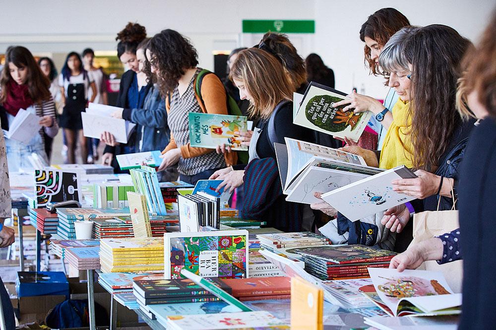 El FLIC Festival 2020 homenajea a los personajes singulares de la literatura ilustrada. Personas, en la feria, consultando libros.